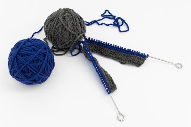Спицы с вязанием, серые и синие шары шерсти на белом фоне