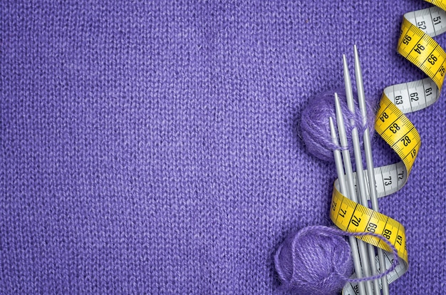 Knitting needles, yellow centimeter, balls of wool on lilac knitted fabric