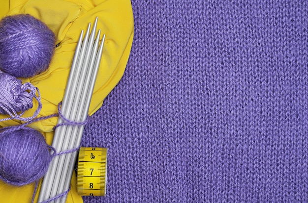 Knitting needles, yellow centimeter, balls of wool, yellow fabric on lilac knitted fabric