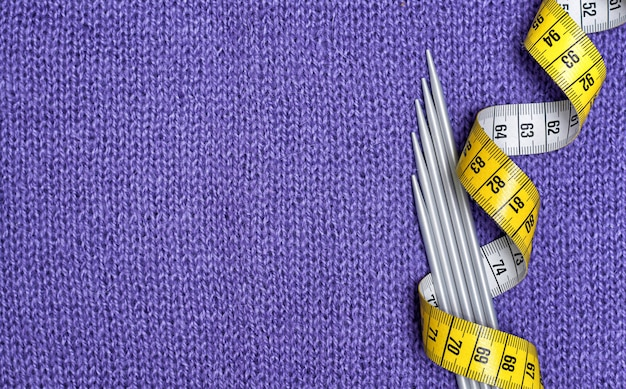 Knitting needles and a yellow centimeter on a lilac knitted fabric