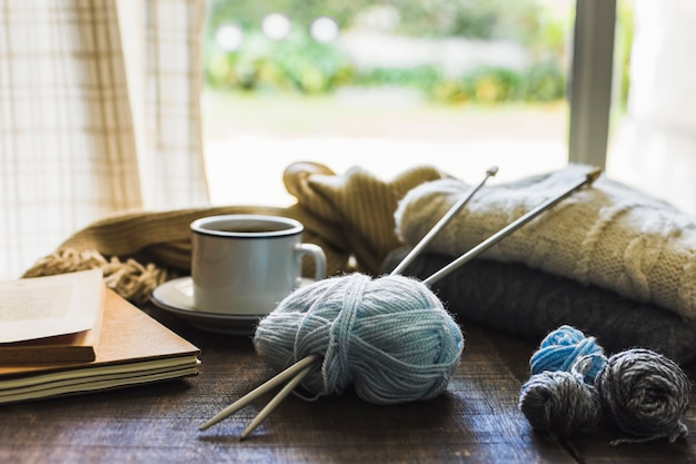 Knitting supplies and beverage near window