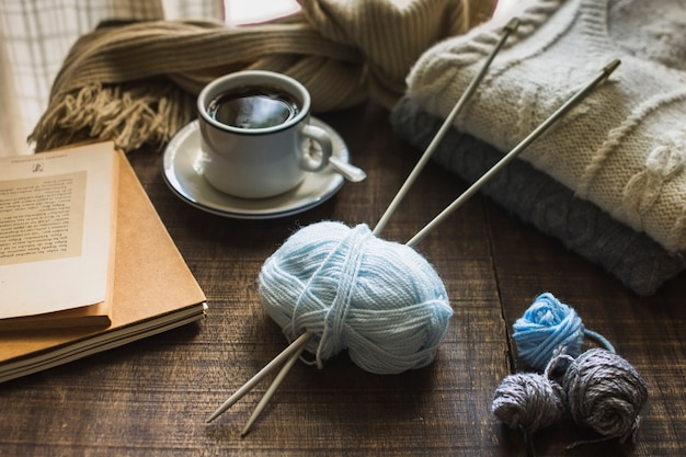 Knitting supplies near hot beverage and books