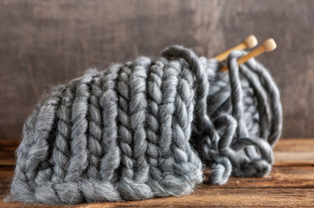 Knitting, thick gray threads on wooden knitting needles, clew and canvas, texture,