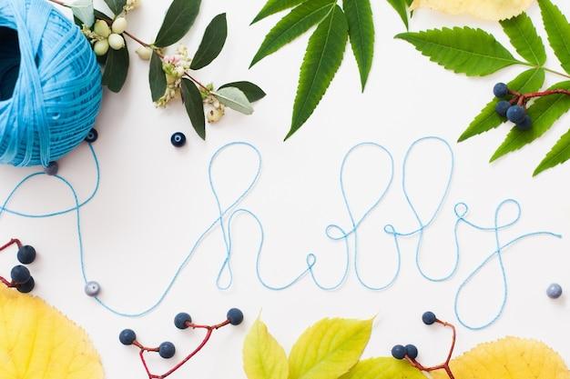 Вязание нитью слово хобби в рамке из листьев