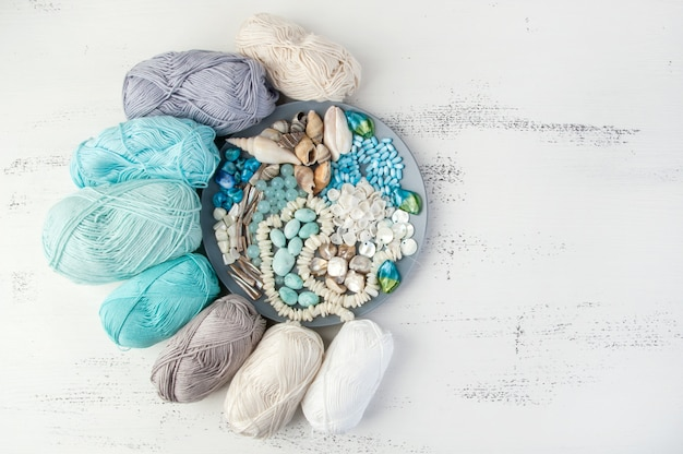 Knitting threads and gray plate with beads and seashells