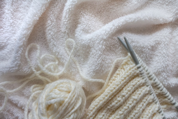 Knitting white wool yarn pattern.