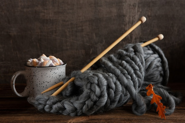 Knitting with thick gray threads on wooden knitting needles and a mug with a hot drink and marshmallows,