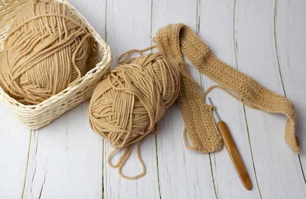 木のかぎ針編みのフックと茶色の綿糸を使った編み物、木の背景に置く