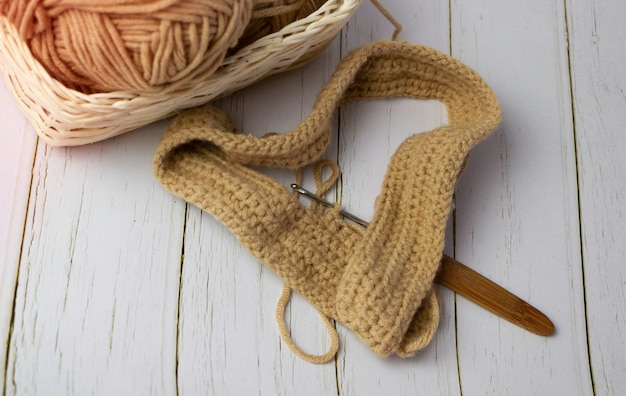木の背景に、ぼやけた綿糸の横に置かれた木製のかぎ針編みのフックを使った編み物
