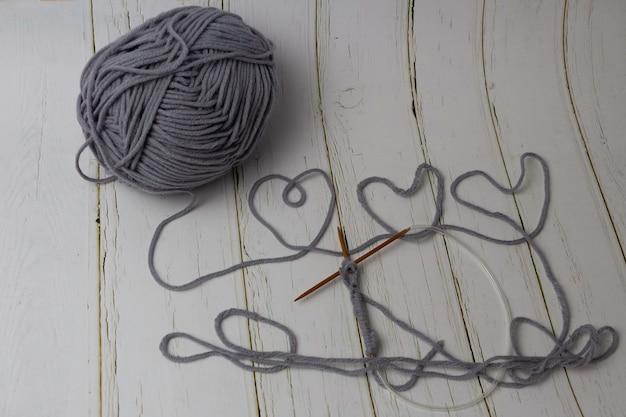 背景に綿糸の横に置かれた木製のかぎ針編みのフックを使った編み物