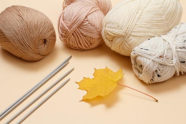 ベージュの背景に毛糸のボール、金属の編み針、乾燥したカエデの葉を編みます。編み物のコンセプト。上面図。