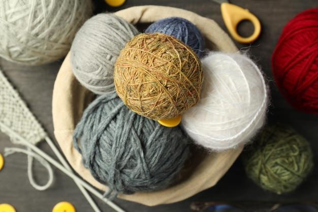 Концепция вязания пряжи на сером деревянном фоне.