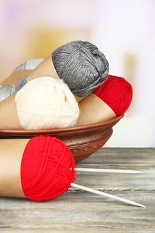 明るい背景で、木製のテーブルに編み針で毛糸を編む