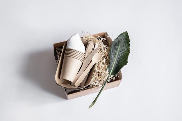 ナイフ、フォーク、カップ、食品用の紙容器、天然の葉。フラットレイ
