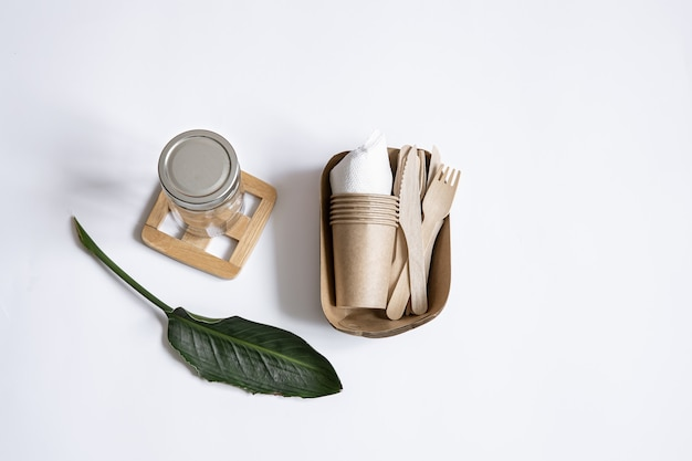 Knives, forks, dishes, glass jar, paper containers for food and a natural leaves. the concept of zero waste and plastic free.