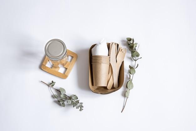 Ножи, вилки, посуда, стеклянная банка, бумажная тара для еды и веточки эвкалипта. концепция без отходов и без пластика.