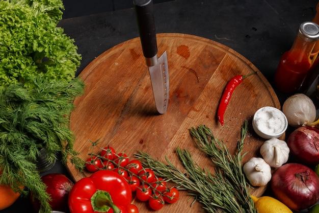 Ножи на деревянной доске. состав различных продуктов для приготовления пищи. вид сверху.