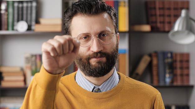 노크 노크, 집에 누구라도 있습니다. 카메라를 보고 카메라를 두드리는 안경을 쓴 회의적인 수염 난 남자 교사 또는 사업가. 미디엄 샷