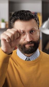 노크 노크, 집에 누구라도 있습니다. 카메라를 보고 카메라를 두드리는 안경을 쓴 회의적인 수염 난 남자 교사 또는 사업가의 수직 보기. 미디엄 샷