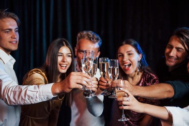ノックグラス。お祝いの服を着た友達のグループが一緒に屋内でパーティーを開きます。