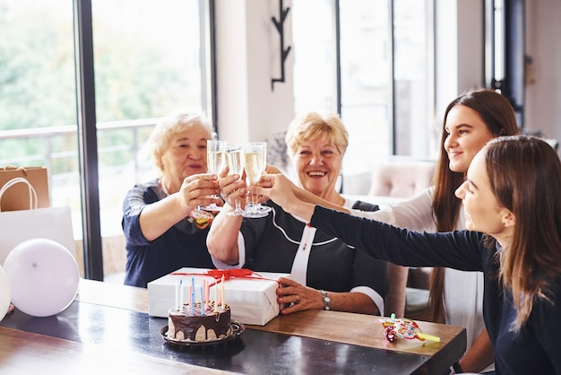 Knocking glasses. senior woman with family and friends celebrating a birthday indoors.