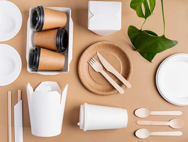 Понятие наклона. экологичная одноразовая посуда с нулевыми отходами, вид сверху, плоская, лежала на коричневом фоне.