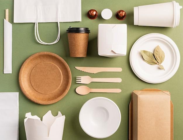 Понятие наклона. экологичная одноразовая посуда с нулевыми отходами, вид сверху, плоская на зеленом фоне. шаблон