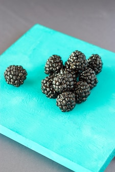 Knot fresh blackberries on wooden blue stand on a gray space. top view. copy space. vertical