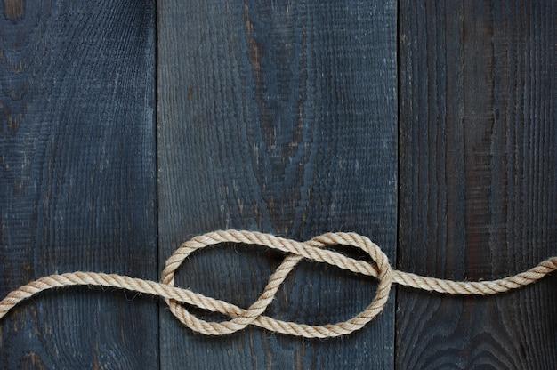 Узел веревки на деревянном фоне