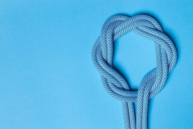 青い背景のロープの結び目。スペースをコピーします。