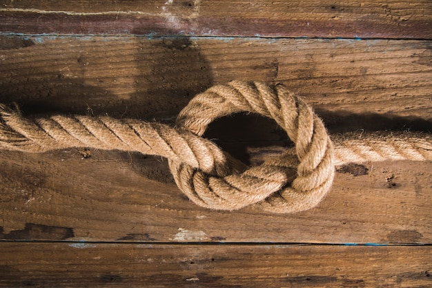 Knot on a rope on a wooden surface.