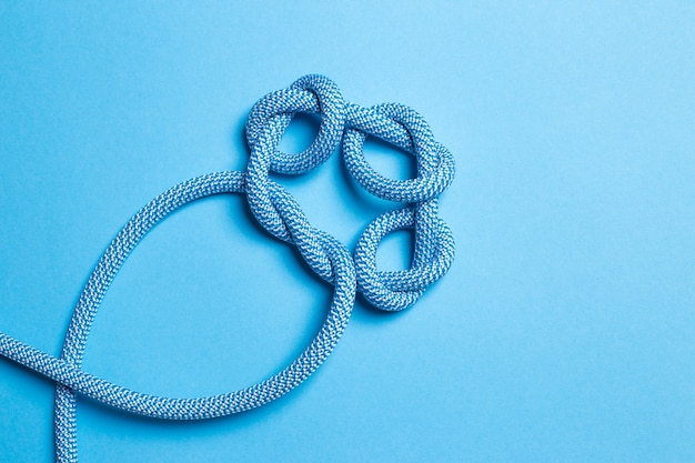 青い背景のロープの結び目。