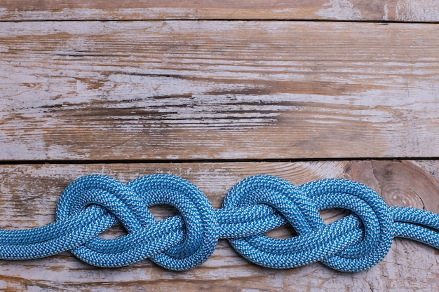 Knots in the shape of an eight on a rope on a wooden background. copy space.