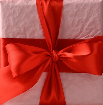 Knotted bow on gift and red silk ribbon, close up
