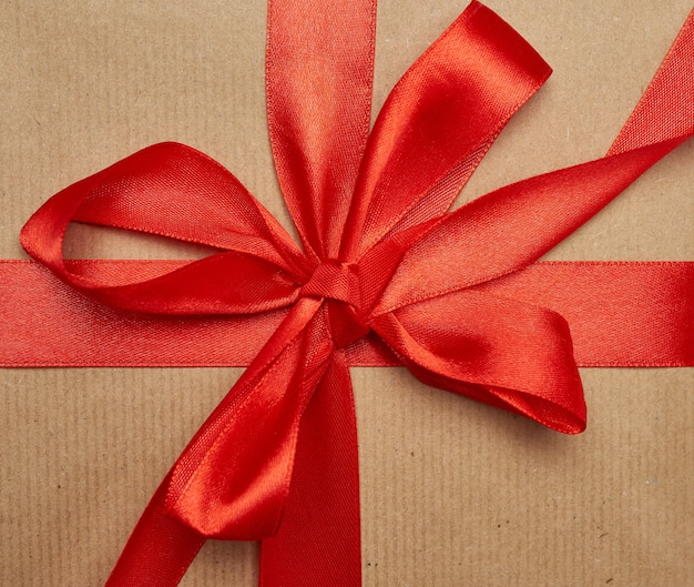 Knotted bow made of red silk ribbon on brown kraft paper