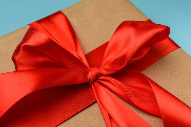 선물 및 빨간 실크 리본에 매듭이있는 활을 닫습니다.