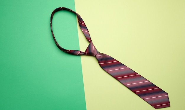 Knotted silk manã¢â€â™s tie on a green background