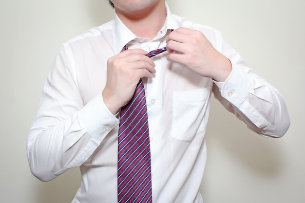 Knotting his tie