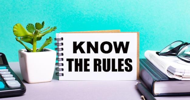 규칙을 아십시오 화분에 심은 꽃, 일기 및 계산기 옆에있는 흰색 카드에 적혀 있습니다. 조직 개념