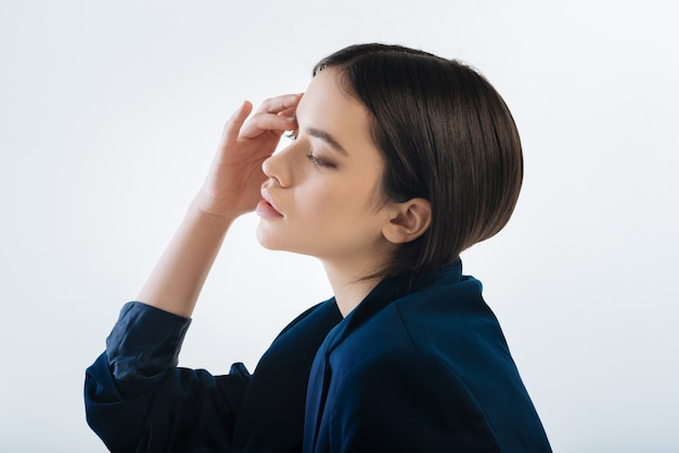 Do not know. worried pleasant young woman touching her head  while turning  in profile and  thinking