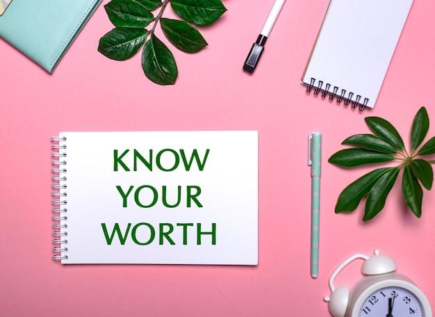 Know your worth는 메모장, 펜, 흰색 알람 시계 및 녹색 잎으로 둘러싸인 분홍색 배경에 흰색 메모장에 녹색으로 쓰여 있습니다. 교육 개념