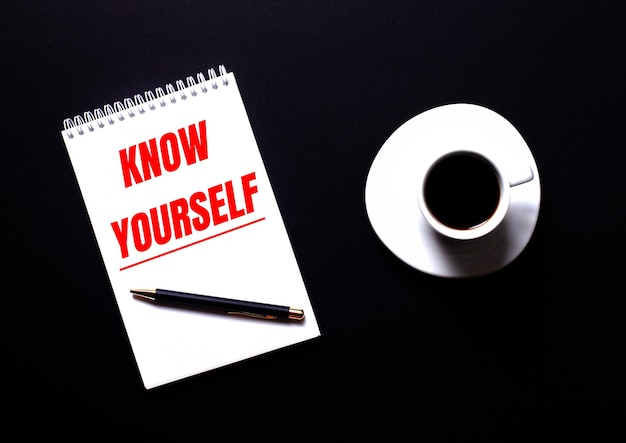 Know yourself is written in a white notebook in red type near a white cup of coffee on a black table. motivational concept
