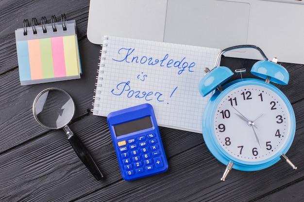 Знание - сила. будильник с калькулятором и стеклянной лупой на темном деревянном столе.