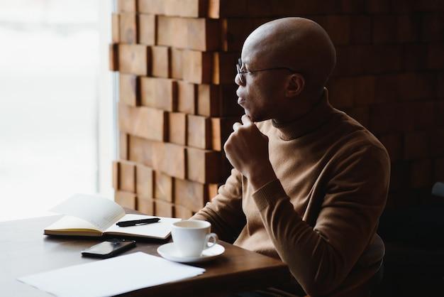 Знания, обучение, образование и технологии. небрежно одетый хардкор-отличник с афро-прической решает математические задачи, сидя за столиком в кафе с учебниками и электронным устройством