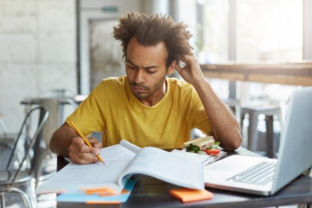 지식, 학습, 교육 및 기술. 수학 문제를 해결하는 아프로 헤어 스타일을 가진 학생, 교과서 및 전자 장치가있는 카페 테이블에 앉아