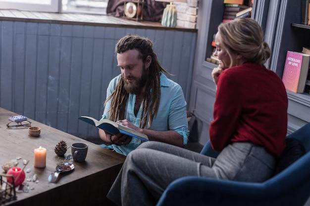 미래에 대한 지식. 방문자와 함께 앉아 특별한 책을 읽는 멋진 똑똑한 점쟁이