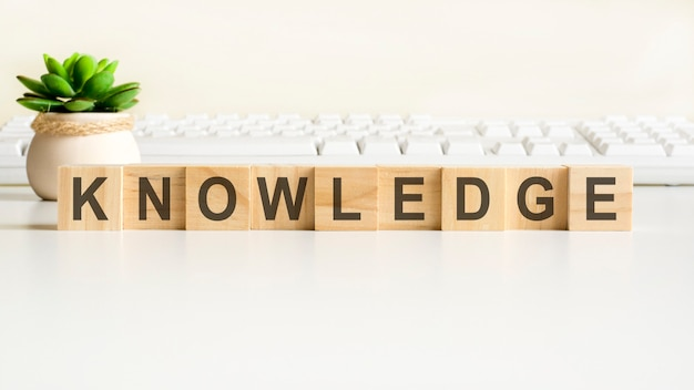 Knowledge word made with wooden blocks. front view concepts, green plant in a flower vase and white keyboard on background
