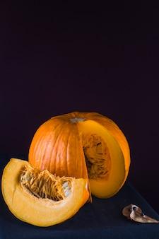 Koelreuteria paniculata and ripe pumpkin slice on black backdrop