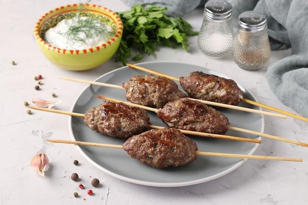 皿の上の木製の串焼きとテーブルの上のソースのコフタケバブ、アラブ料理の伝統的な料理、グリルしたミンチ肉のシシカバブ、クローズアップ