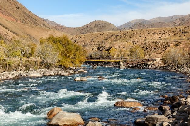 Kokemeren river, djumgal kyrgyzstan, broken bridge on the river, beautiful landscape